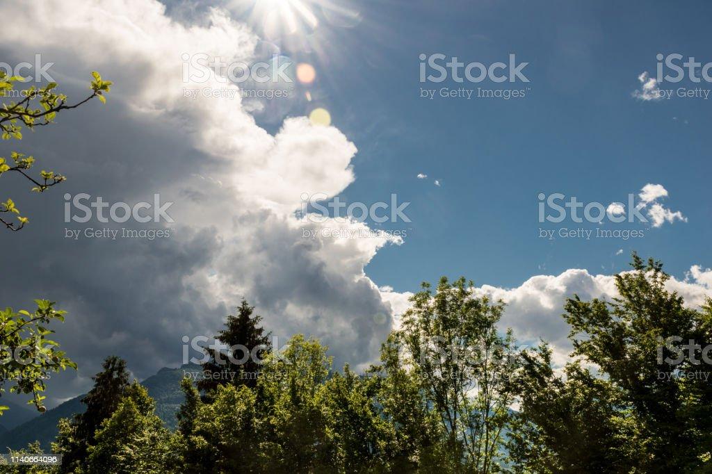 Sun Shining Through Storm Cloud over Mountains