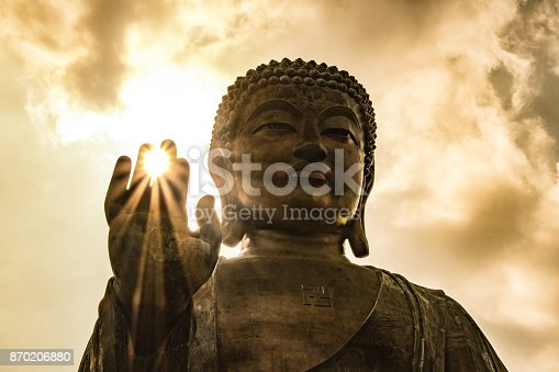 Sun shining through Tian Tan Giant Buddha on hillside in Hong Kong