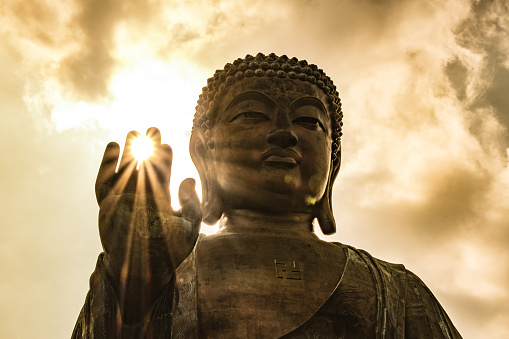 Sun shining through Tian Tan Giant Buddha on hillside in Hong Kong