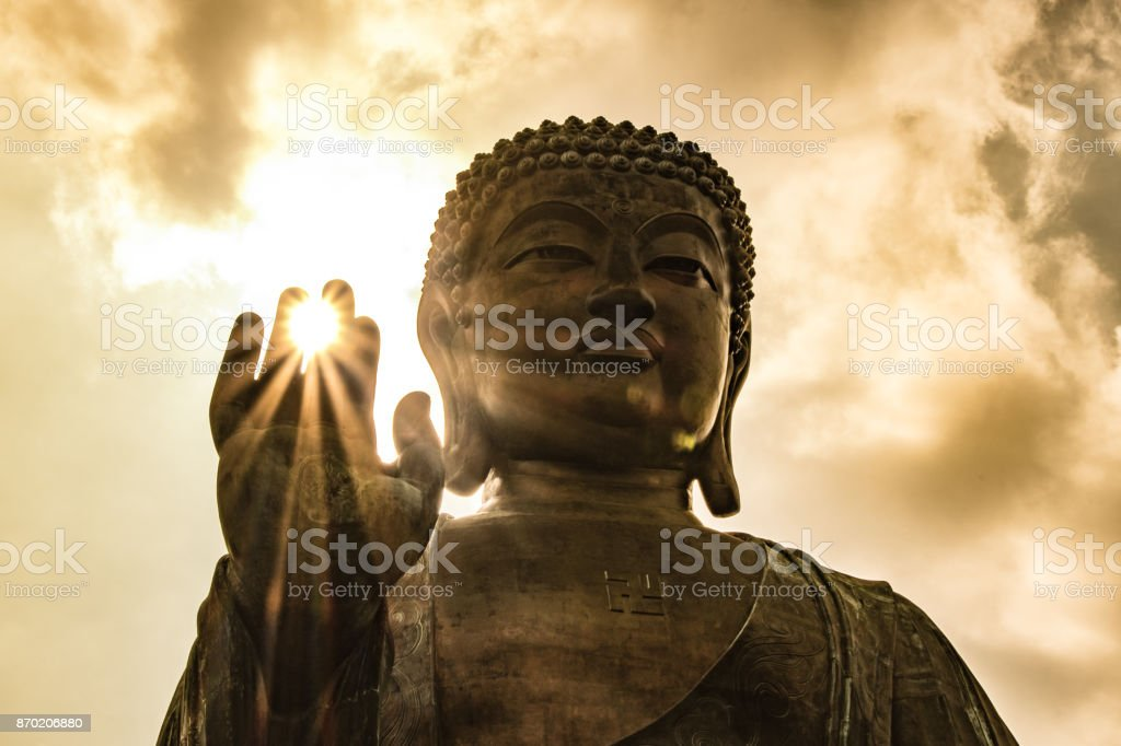 Sun shining through Tian Tan Giant Buddha on hillside in Hong Kong stock photo