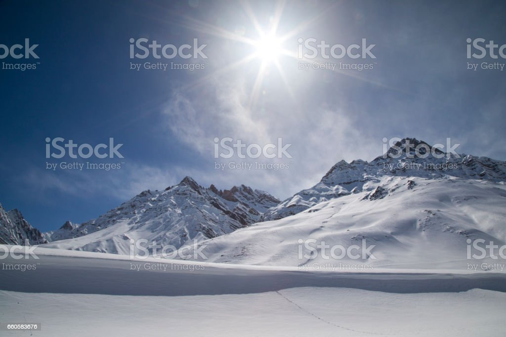 Sun shining with lens flare over snowcapped Himalayas mountain stock photo