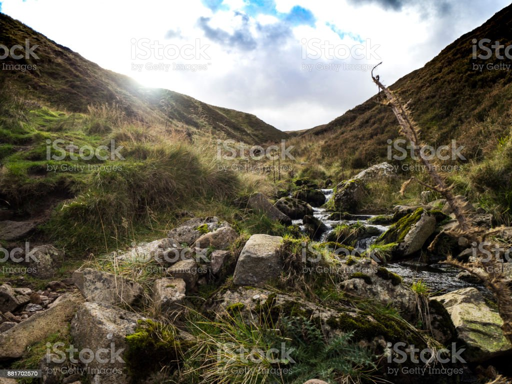 Sun showing over Stream & Rocks stock photo