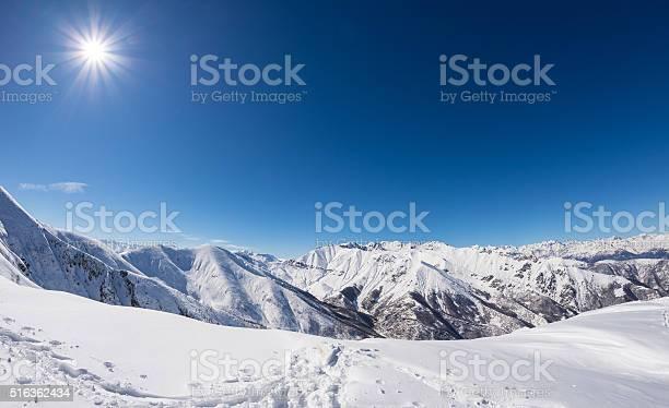 Photo of Sun star glowing over snowcapped mountain range, italian Alps