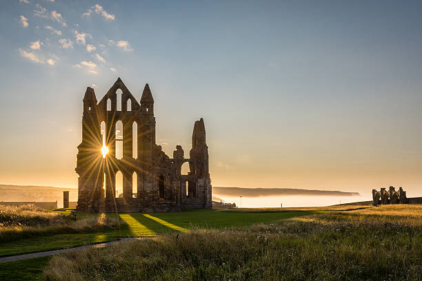 Sun Star on Whitby Abbey The Gothic ruins of Whitby Abbey with the suns rays producing a star.  Sea mist held back by the cliffs at Sandsend in the background abbey monastery stock pictures, royalty-free photos & images