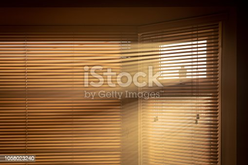 Sun streaming through blinds into a smoky room