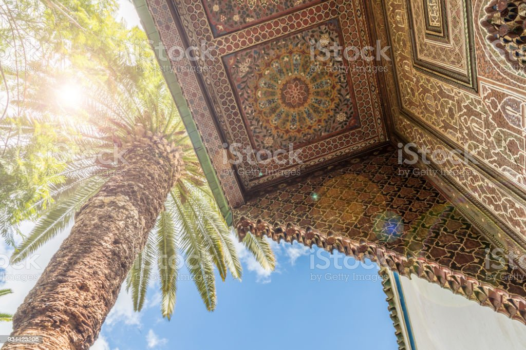 Sun through a large palm tree and ornate shutter/balcony in Marrakesh stock photo