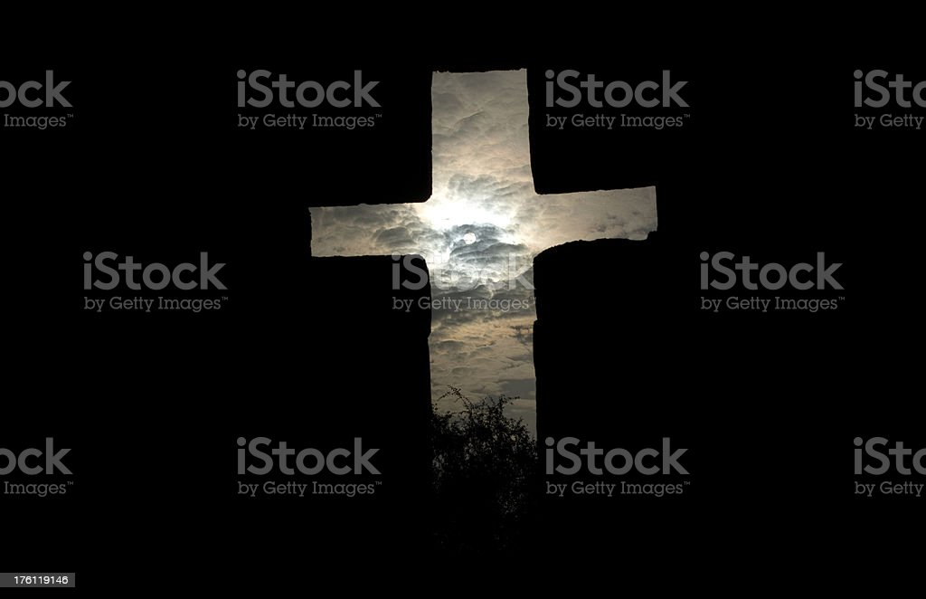View of clouds and sun through the cross shaped window of a partially...