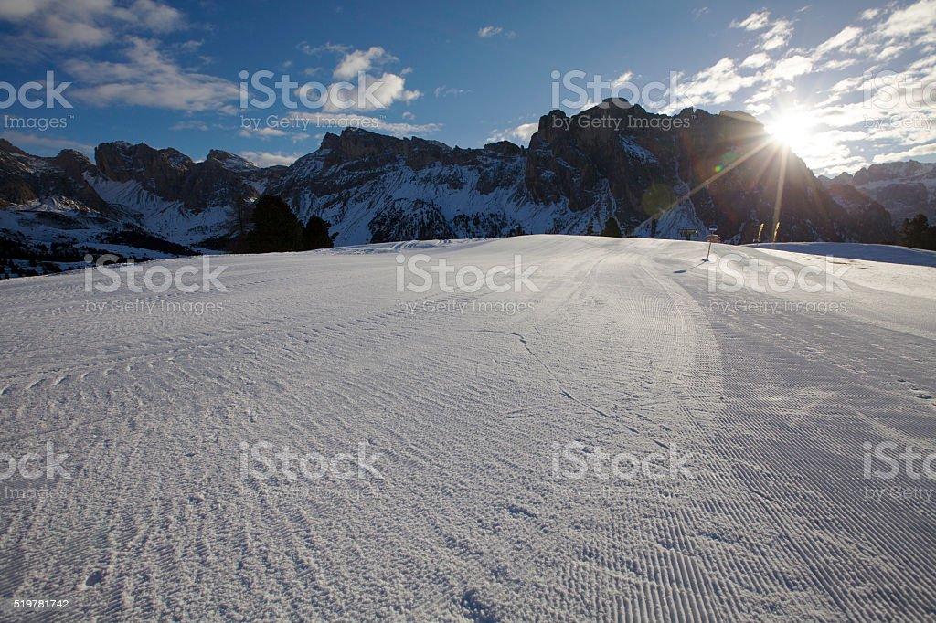 Sun through Dolomites mountains on a skiing slope, Italy stock photo