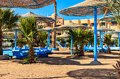 Hurghada, Egypt - December 12, 2018: Sun umbrellas and chaise lounges on tropical beach. Concept of rest, relaxation, holidays, resort