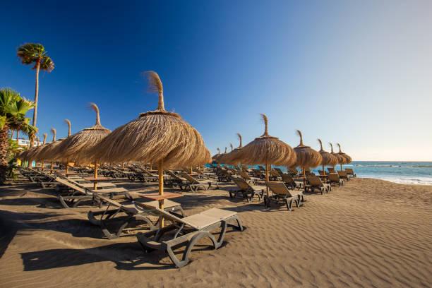 Sun umbrellas Torviscas Beach (Playa de Torviscas), near El Duque Castle, Tenerife, Spain. stock photo