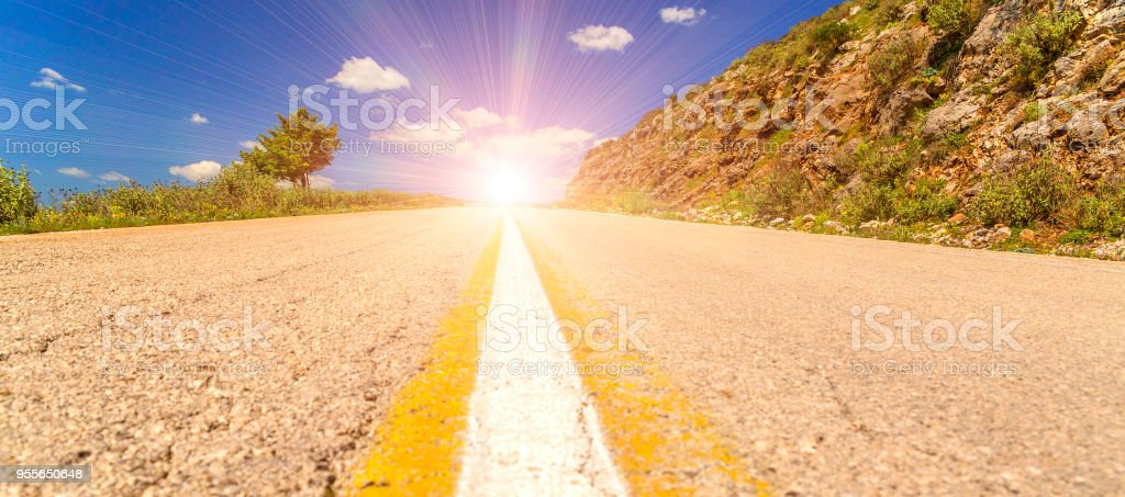 sun uphill asphalt road in among trees spirng time Ioannina Greece stock photo
