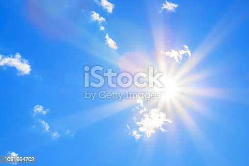 Bright sun with beautiful beams in the blue sky with some light clouds. Space for copy.