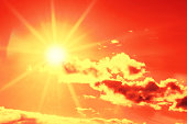 Bright sun with beautiful beams in the sky with clouds. Toned in orange color, space for copy. High resolution - 50 megapixels.