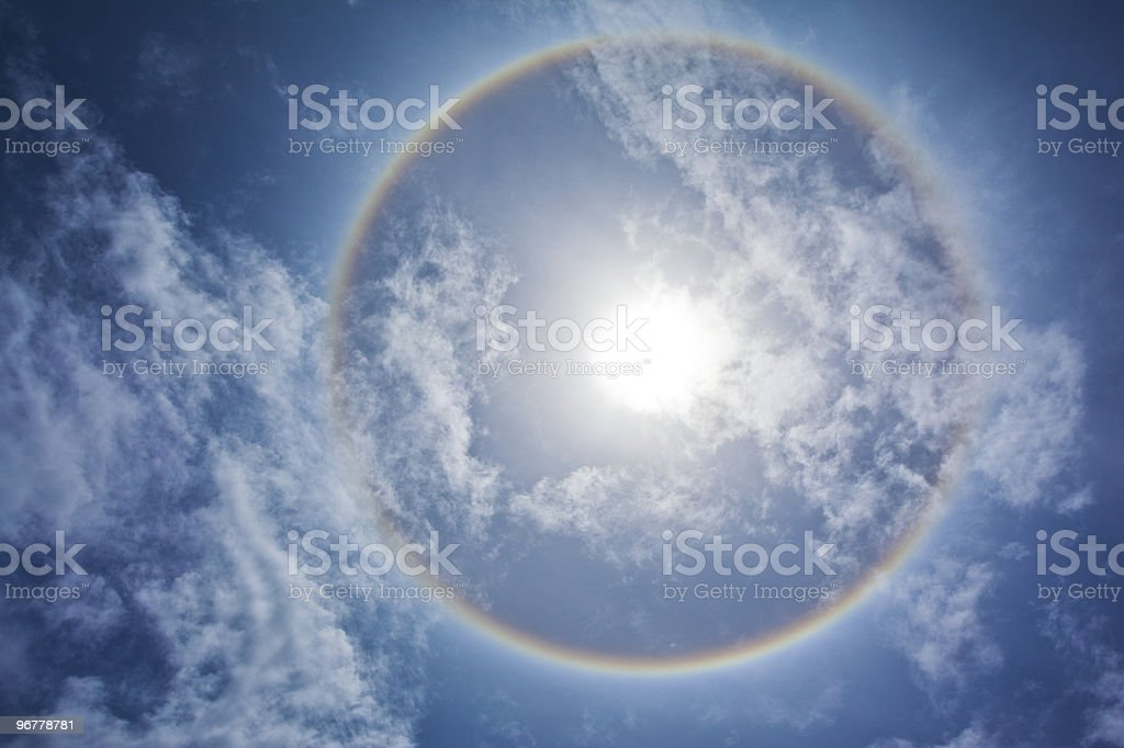 Sun with circular rainbow and clouds stock photo
