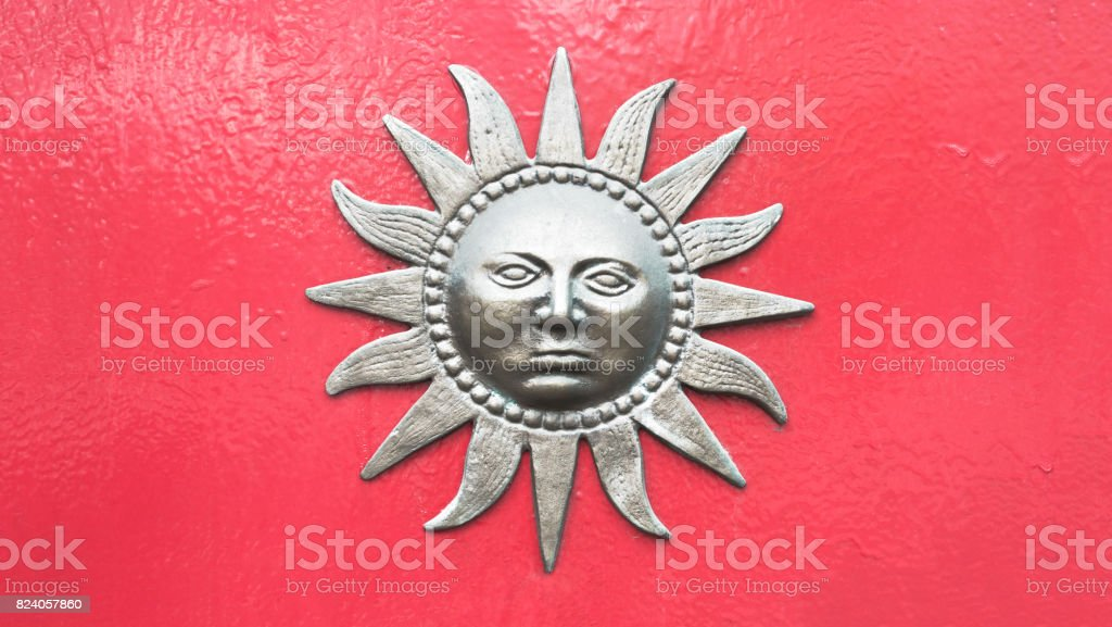 Sun with face ornament on wall stock photo