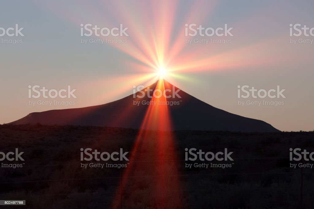 Sun with flare and silhouette of hill peak stock photo