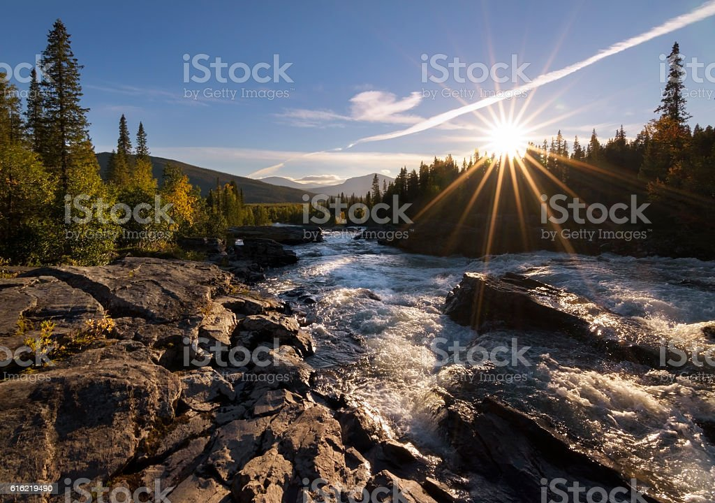 Sun with sun rays giving golden glow to river landscape stock photo