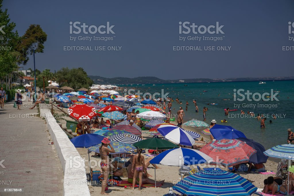Sunbathers on a beach with beach umbrellas at Chalkidiki peninsula. stock photo