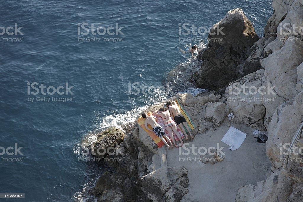 Sunbathers on a cliff. stock photo
