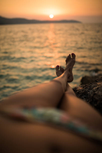 sunbathing at the end of hot summer day - woman leg beach pov stock photos and pictures
