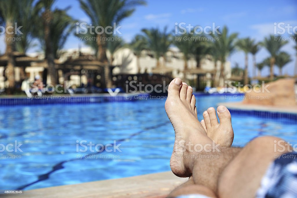 Sunbathing by swimming pool stock photo