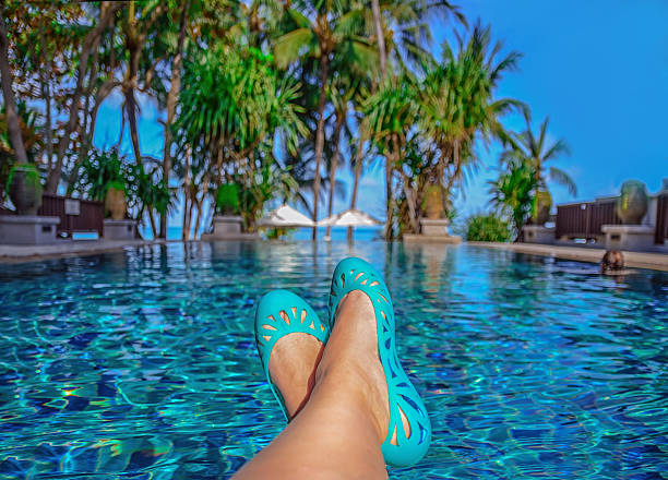 sunbathing by the hotel tourist resort swimming pool . - woman leg beach pov stock photos and pictures