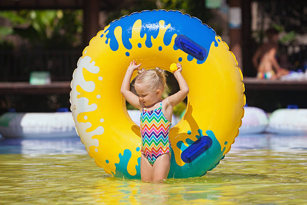 Sunbathing child swim with inflatable toy in swimming pool stock photo