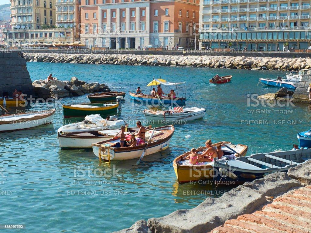 Sunbathing in fishing boats of Borgo Marinari. Naples. Italy. stock photo