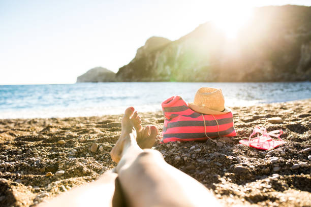 sunbathing legs on hot summer day - woman leg beach pov stock photos and pictures