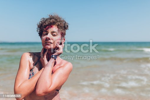 Young, attractive woman, covered with body paint, standing on the beach, sunbathing, enjoying. Albena, Bulgaria.