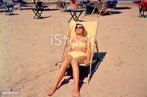 Rimini, Emilia-Romagna, Italy, 1960. A young lady from the north of Europe enjoys the sun of the south in a deck chair.