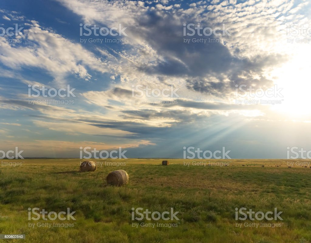 Sunbeam Light Rays Shining Down on Country Landscape Afternoon Light Beams Shining out of the Clouds Over Farmland Agricultural Equipment Stock Photo