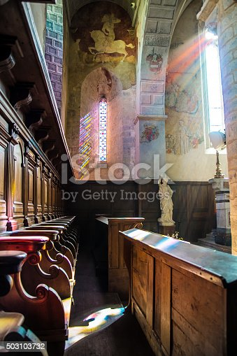 691464522 istock photo Sunbeam through colored stained glass in church illuminates wooden stalls 503103732