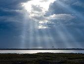 Sunbeam through dark clouds, lake forest, backlit