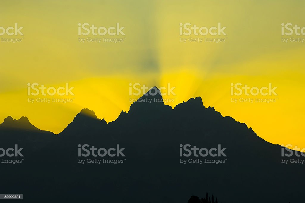 Sonnenstrahlen tauchen über die Berge bei Sonnenuntergang Lizenzfreies stock-foto