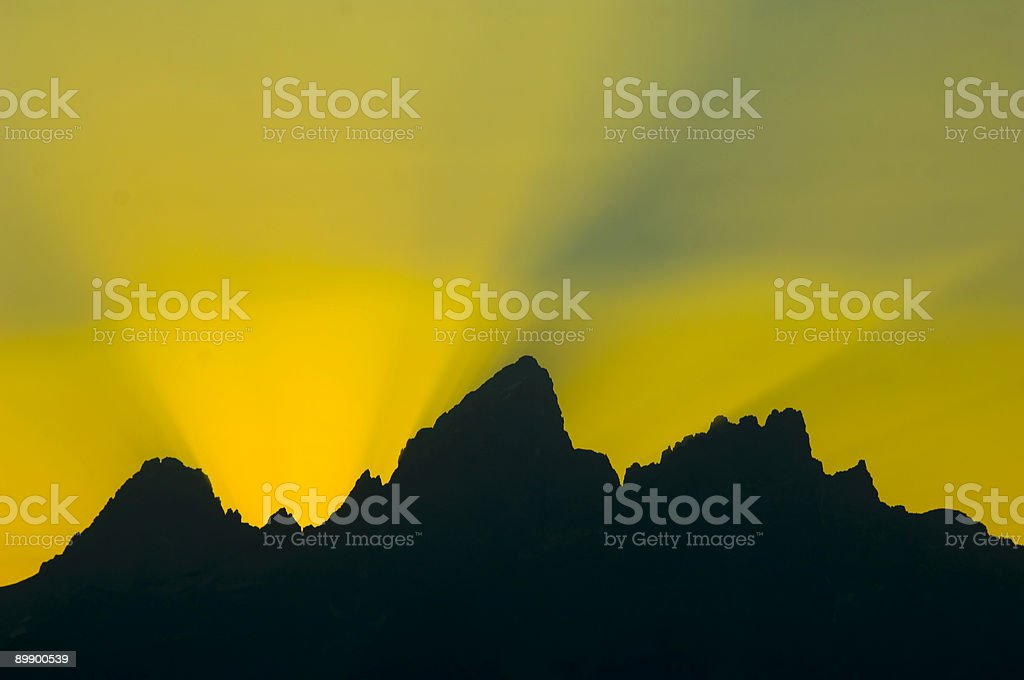 Sunbeams burst over mountains at sunset royalty-free stock photo