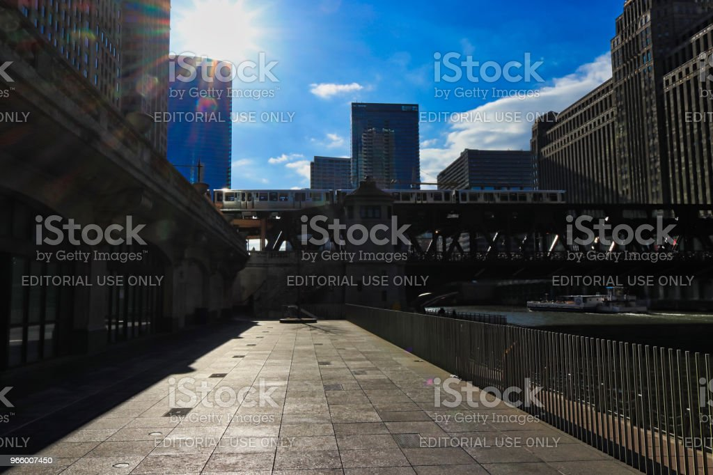 Sunbeams extend over moving el train over the Chicago River and riverwalk during evening commute. - Royalty-free Bridge - Built Structure Stock Photo