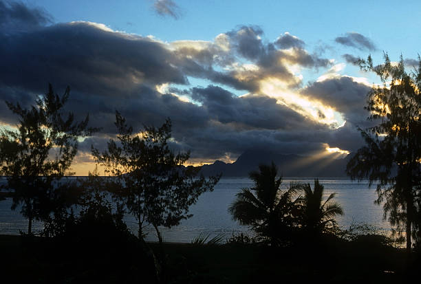 Sunbeams over the South Pacific Sun streaming through the clouds over a South Pacific island. hearkencreative stock pictures, royalty-free photos & images