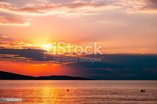 Sun behind the clouds at sunset above the golded colored sea surface