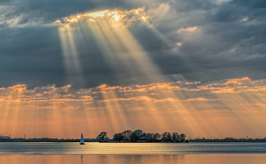 Sunbeams through cloudscape on lake. Location: Lake Steinhuder Meer, Lower Saxony, Germany.