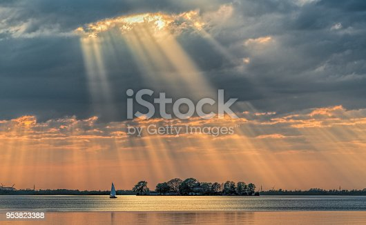Sunbeams through cloudscape on lake. Location: Lake Steinhuder Meer, Lower Saxony, Germany.
