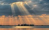 Sunbeams through cloudscape on lake.