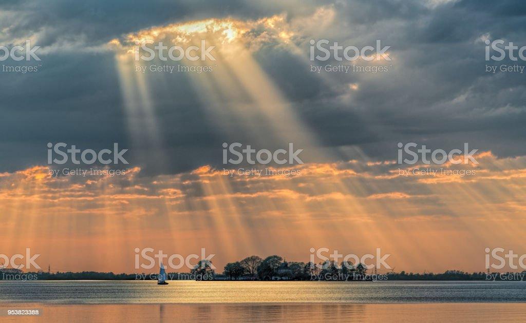 Sonnenstrahlen durch Wolkengebilde auf See. – Foto