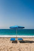 Empty sunbeds and umbrella on the beach on Potali beach, Karpathos Greece