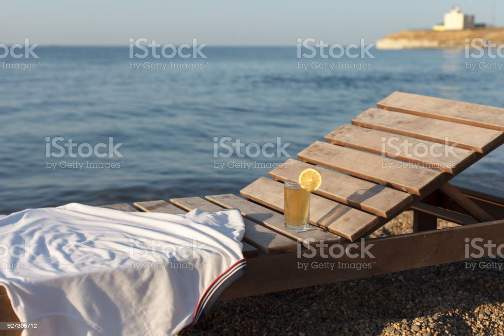 Sunbed with polo shirt and glass of cold drink on it at sea beach White polo shirt and glass of cold drink on sunbed at pebble sea beach at dawn Beach Stock Photo