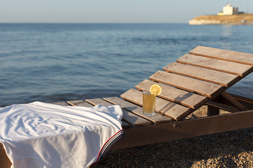 Sunbed With Polo Shirt And Glass Of Cold Drink On It At Sea Beach Stock Photo - Download Image Now