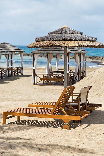 sonnenliegen und strohhut mit schirm für entspannung am meer strand - hochzeitsreise zypern stock-fotos und bilder