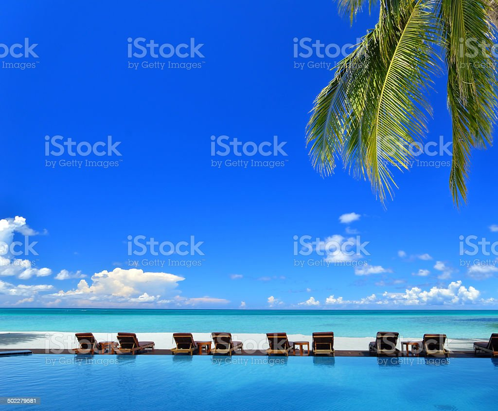 Sunbeds beside swimming pool in tropical beach resorts stock photo