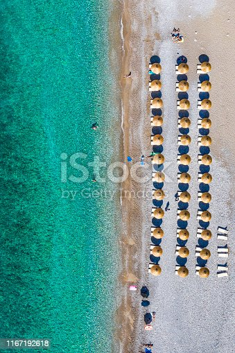 999001484 istock photo Sunbeds on a beach shoreline, as viewed from a drone point of view 1167192618