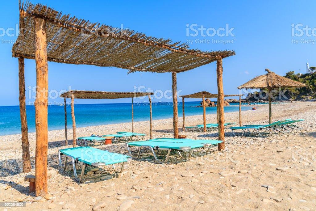 Sunbeds on Potami beach, Samos island, Greece stock photo